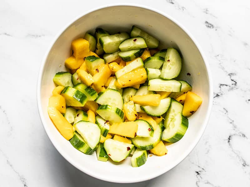 Finished cucumber mango salad in a white bowl