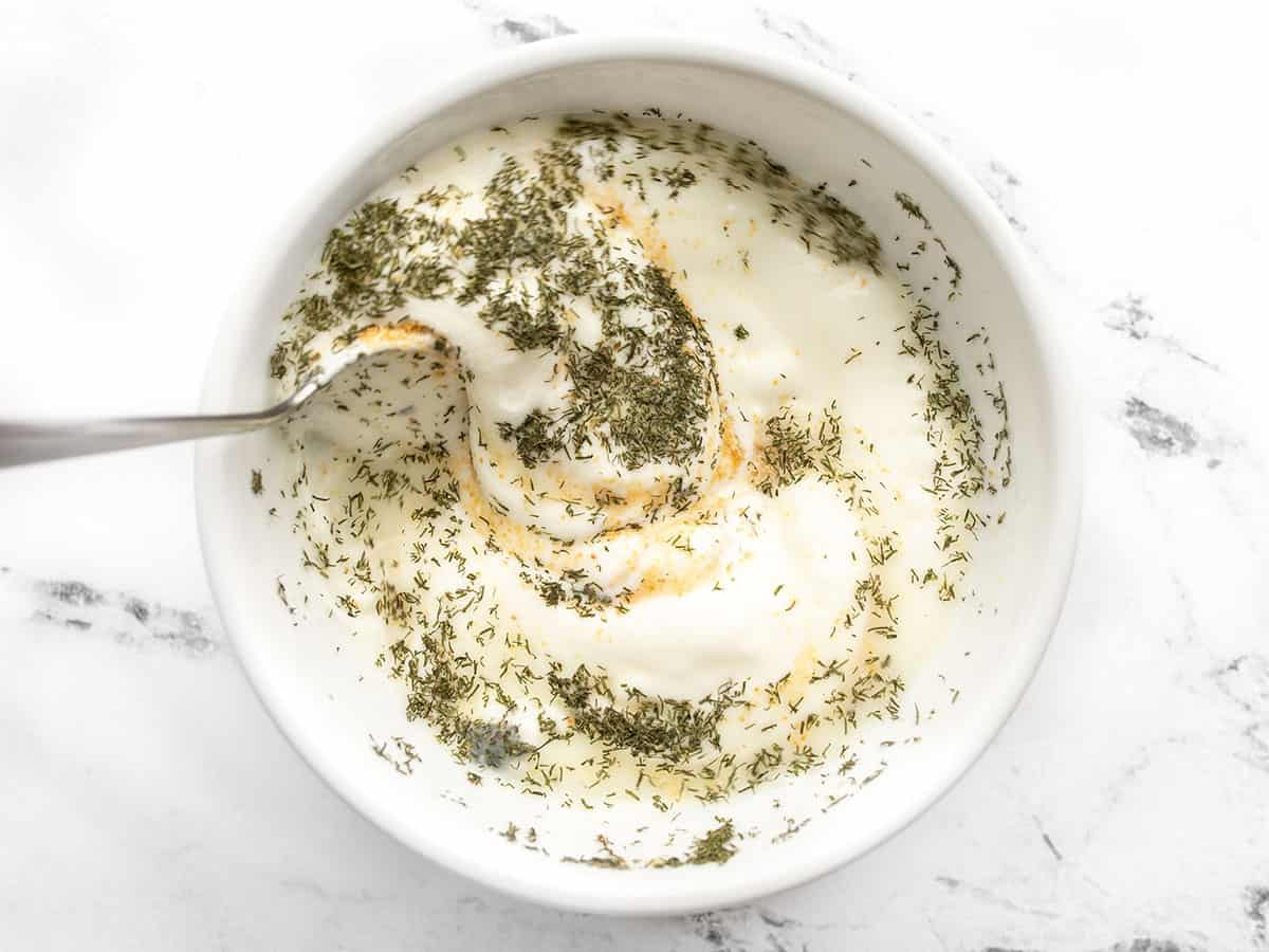 lemon, garlic powder, and dried dill being stirred into yogurt
