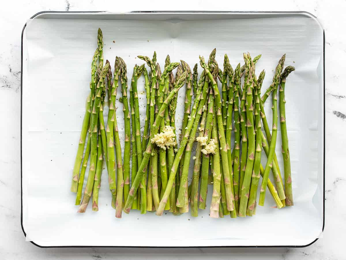 asparagus, garlic, oil, and salt on a baking sheet