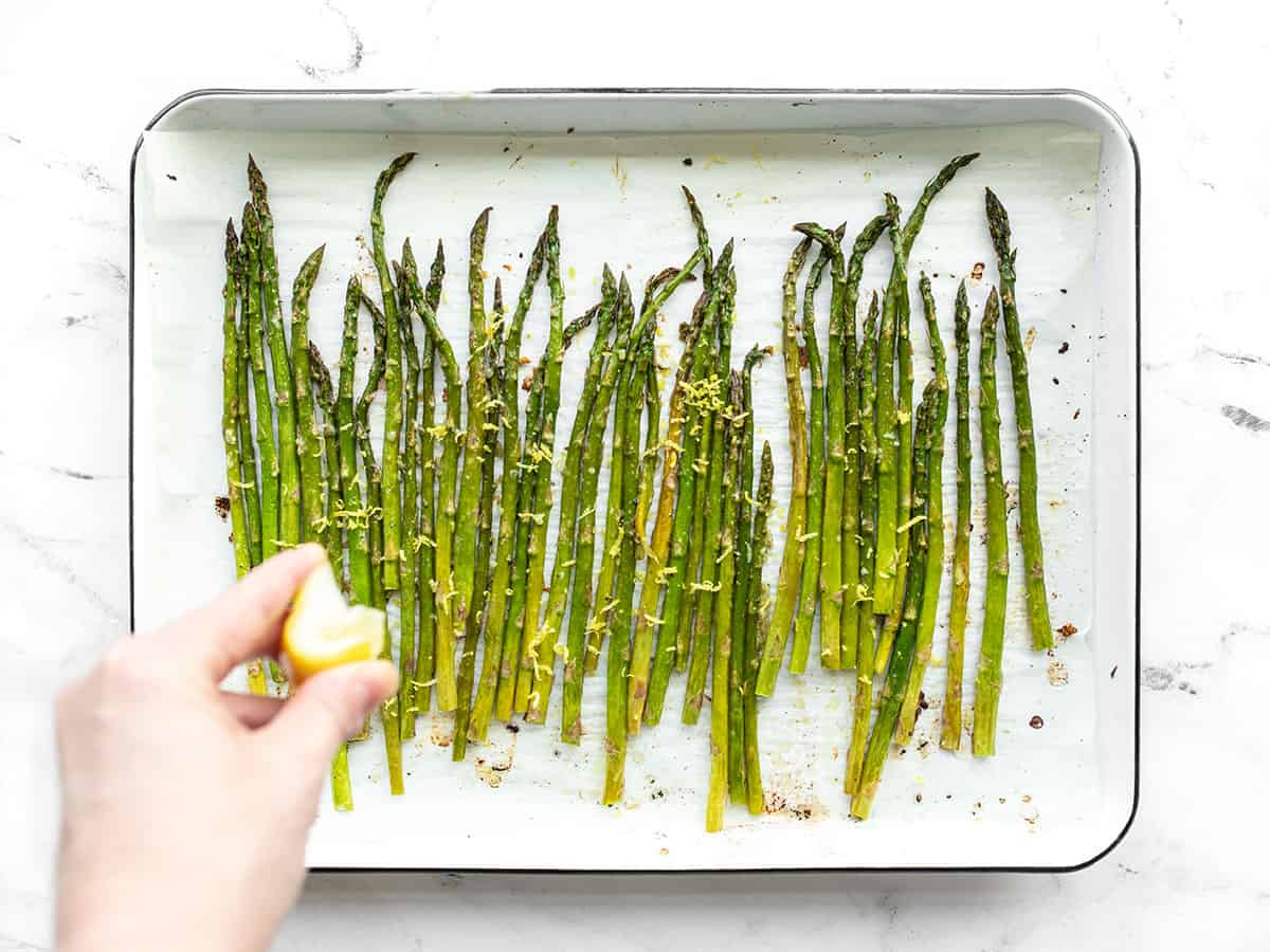 Lemon being squeezed on roasted asparagus