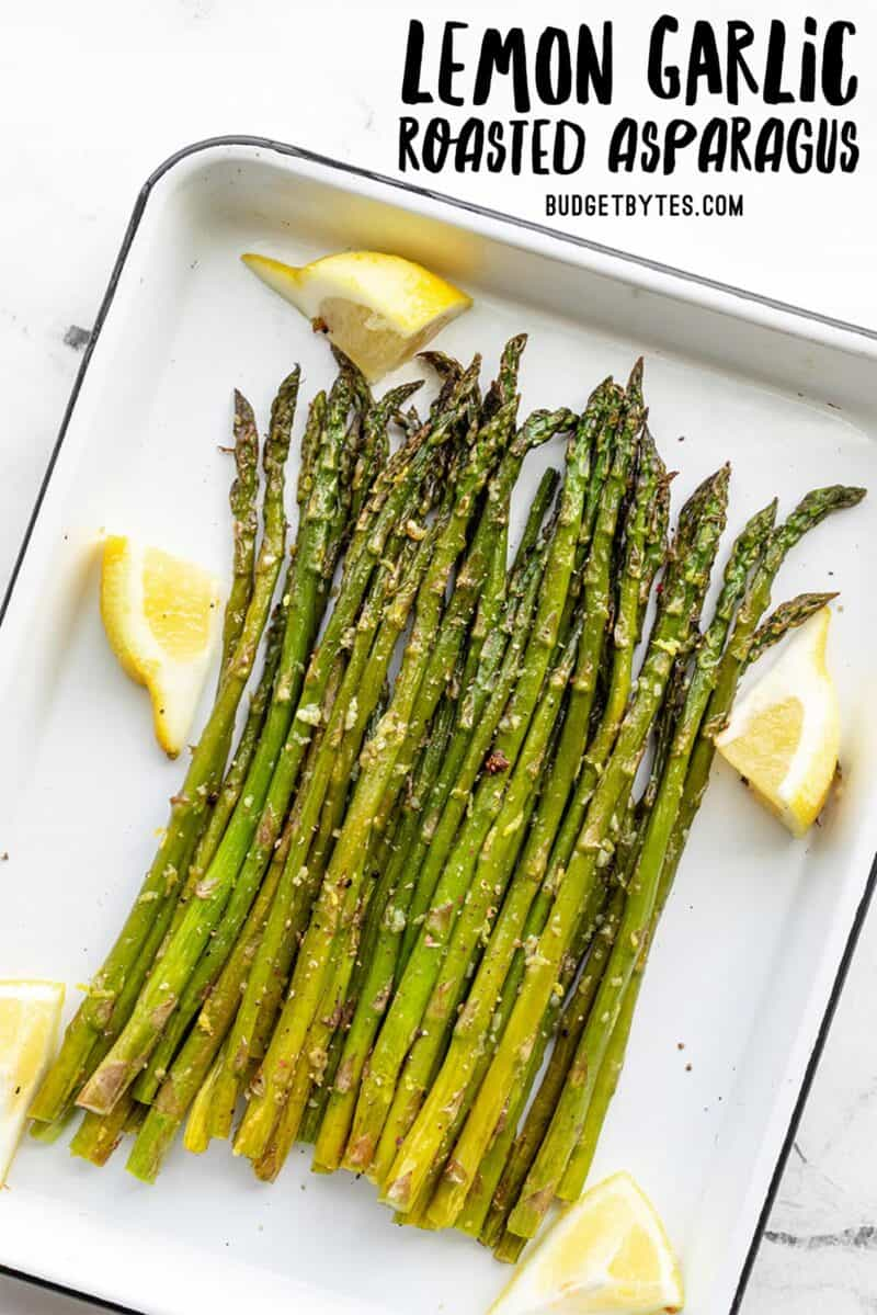 Roasted asparagus on a white sheet pan with lemon wedges, title text at the top