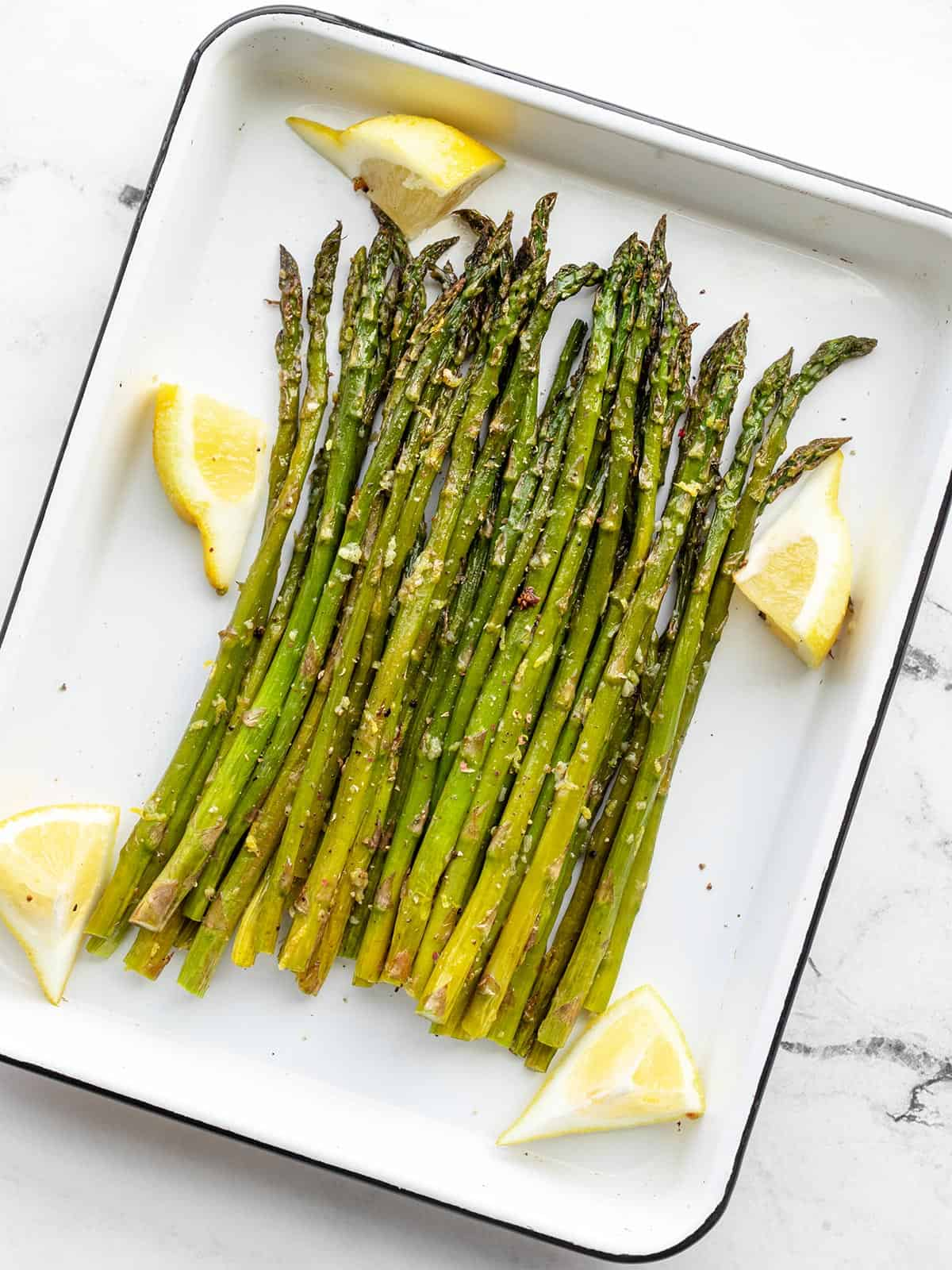 Lemon Garlic Roasted Asparagus on a white roasting pan with lemon wedges