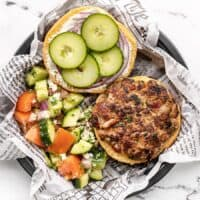Overhead view of an open faced Mediterranean Turkey Burger on a paper lined plate with cucumber salad on the side