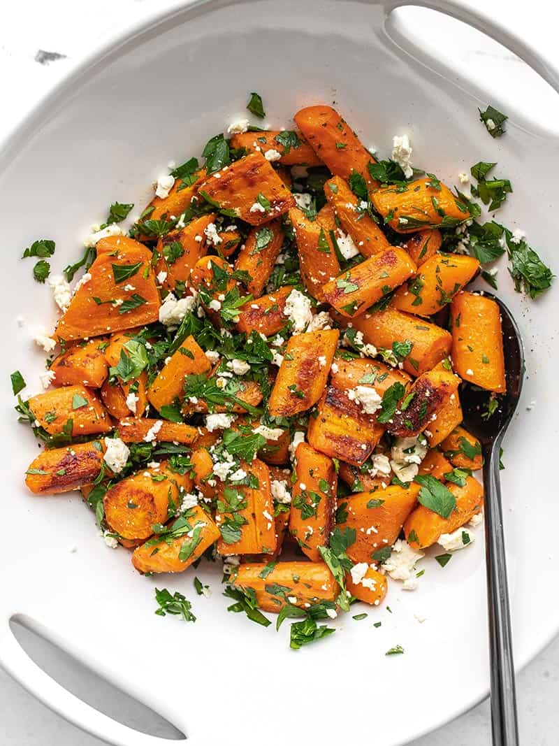 A white serving bowl full of Roasted Carrot and Feta Salad, a black spoon in the side.