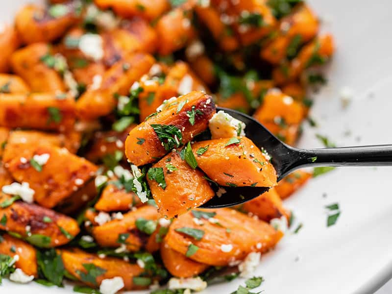 Close up of Roasted Carrot and Feta Salad, a spoon holding a few pieces close to the camera