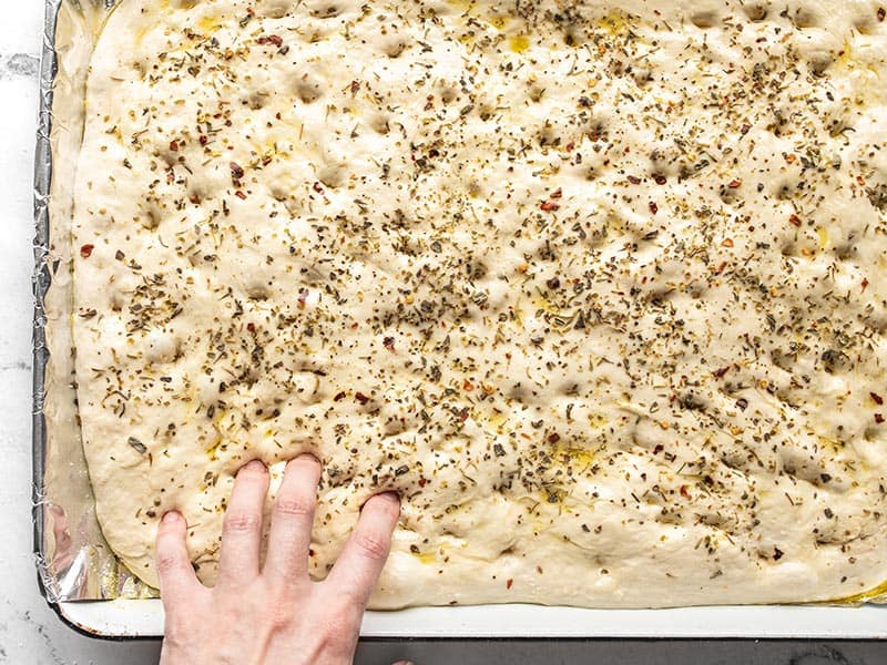 Fingers making indentations in unbaked focaccia