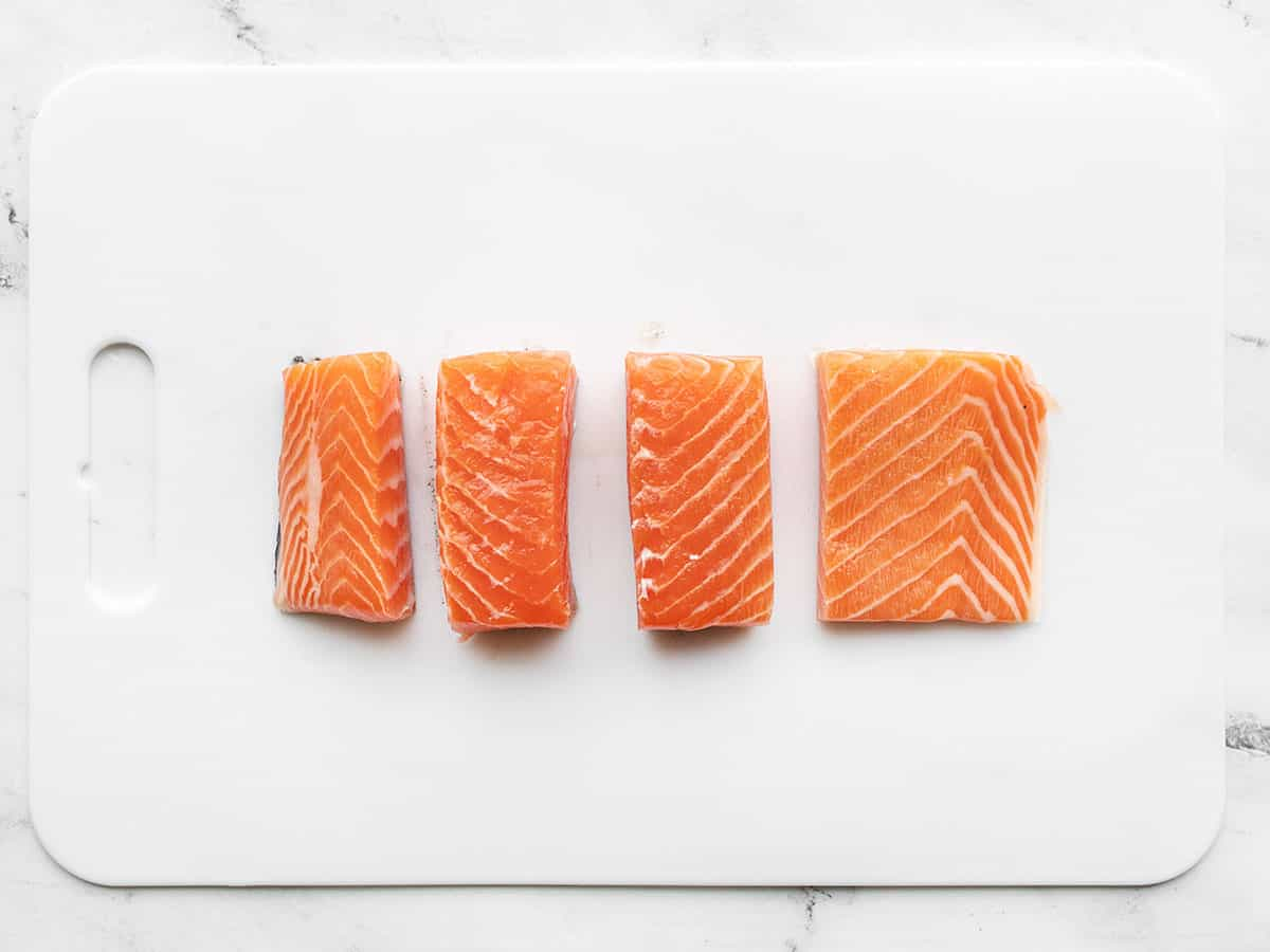 Salmon fillet cut into four portions on a cutting board