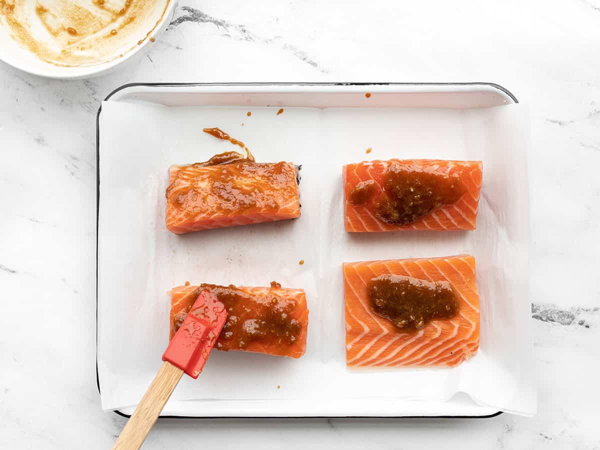 Glaze being spread onto salmon portions