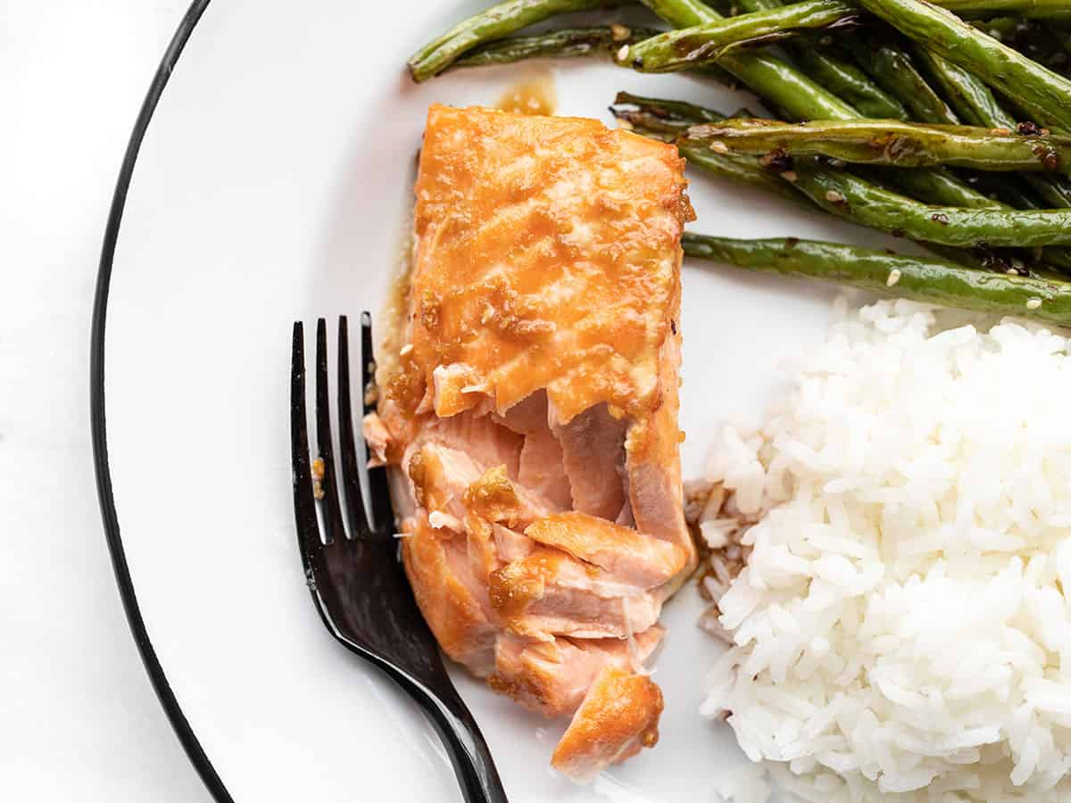 a flaked piece of baked ginger salmon on a plate with green beans and rice