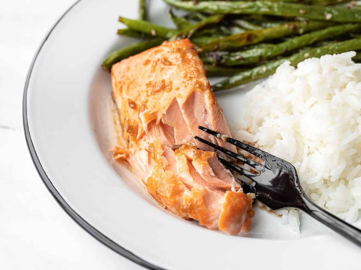Side view of baked ginger salmon on a plate with green beans and rice