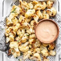 Overhead of garlic parmesan roasted cauliflower on a tray with a bowl of dip