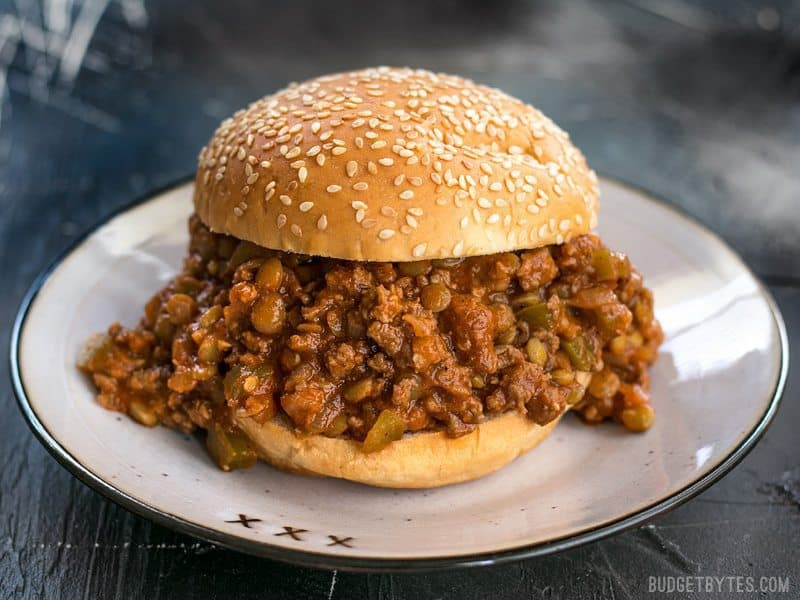 Soft Sesame Seed Bun Stuffed Full of Homemade Sloppy Joes Plus on Plate