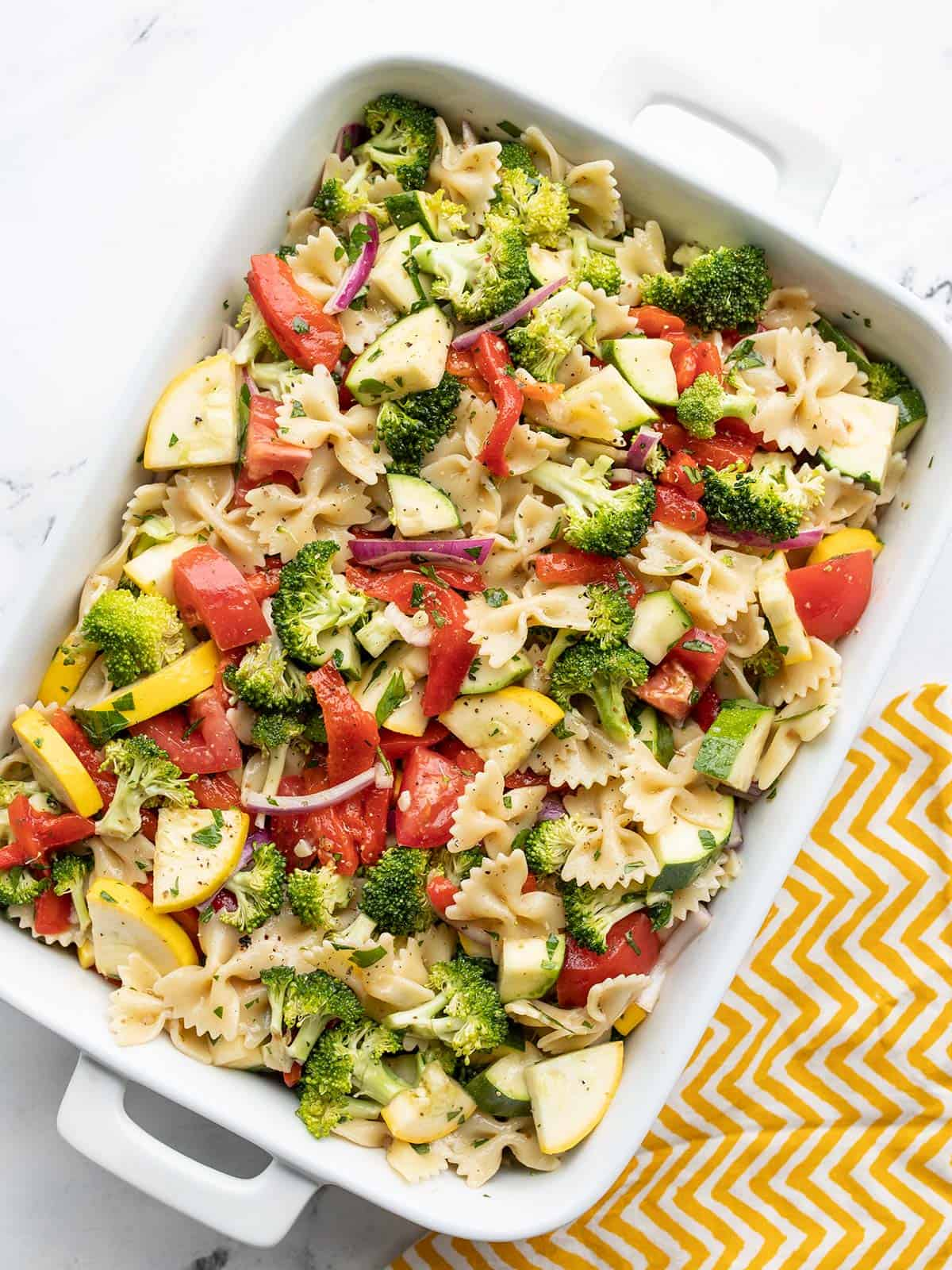 Overhead view of summer vegetable pasta salad in a rectangular casserole dish