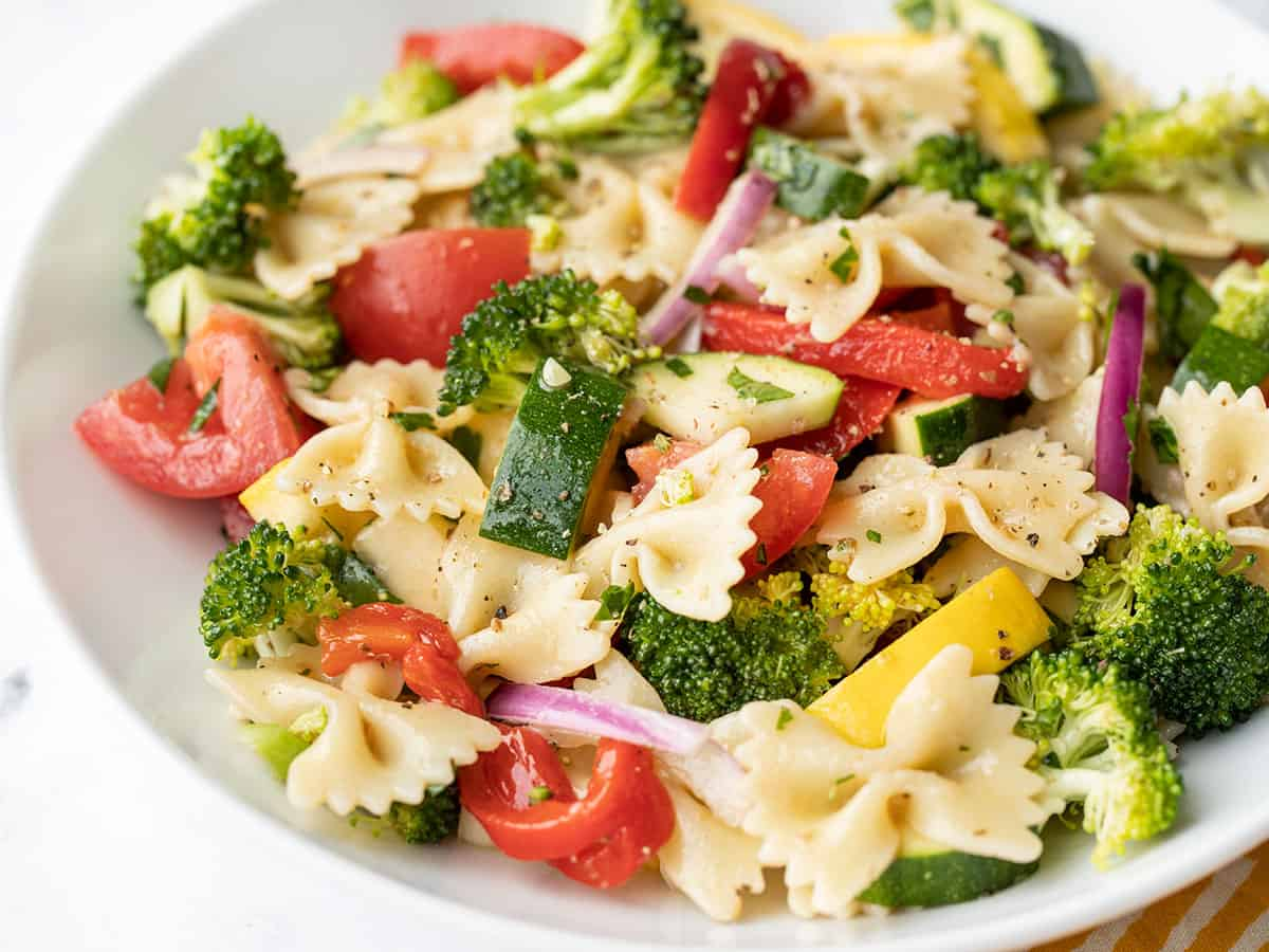 close up side view of a bowl of summer vegetable pasta salad