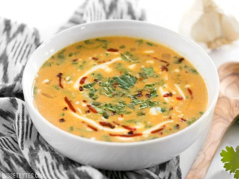 White bowl full of Spicy Coconut and Pumpkin Soup with wooden spoon on the side