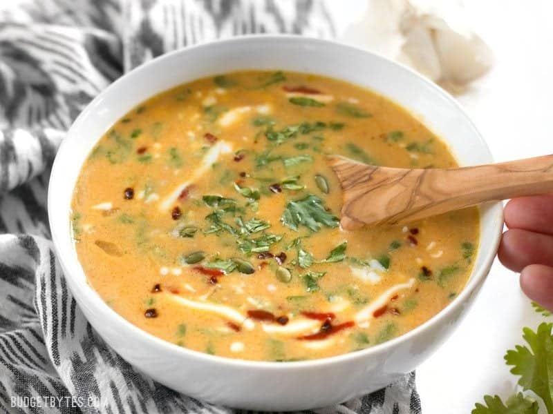 White bowl full of Spicy Coconut and Pumpkin Soup with spoon