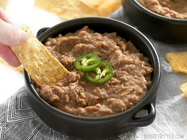 Chips being dipped into slow cooker (not) Refried Beans