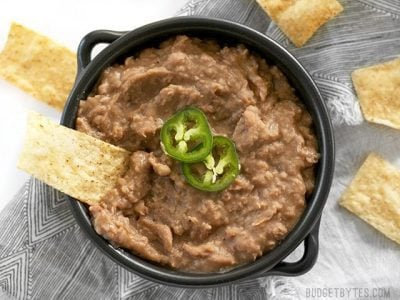 Use your slow cooker to make these low fat and incredibly flavorful (not) refried beans and barely lift a finger. BudgetBytes.com