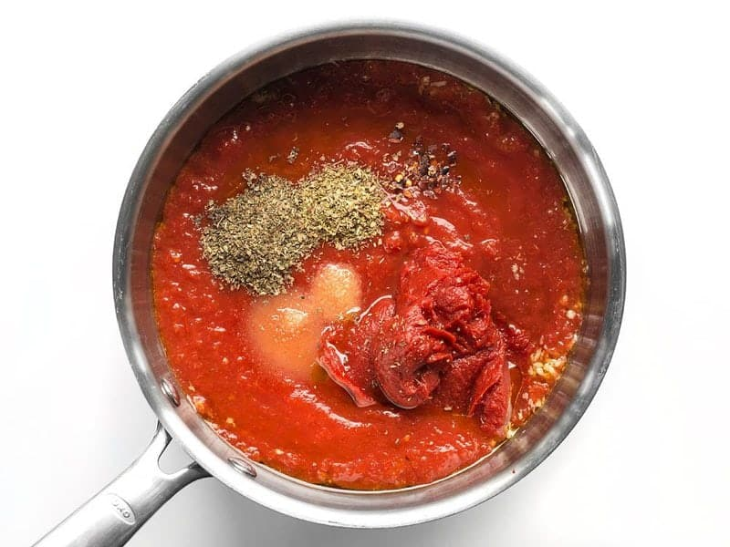 Tomatoes, spices, and herbs in the sauce pot