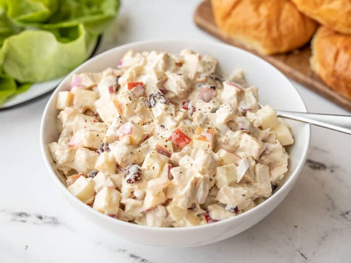 Side view of a bowl of chicken salad with apples, croissants in the background