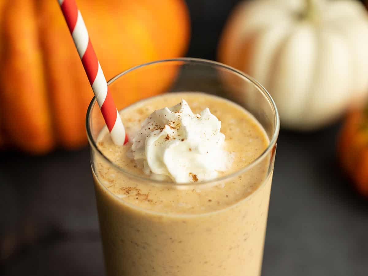 Side view of a pumpkin smoothie in a glass with a straw
