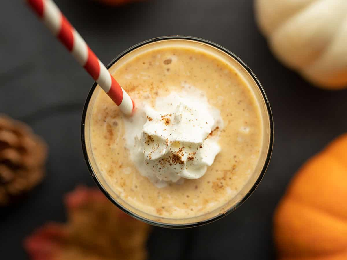 overhead view of pumpkin pie smoothie in the glass with a straw and whipped cream