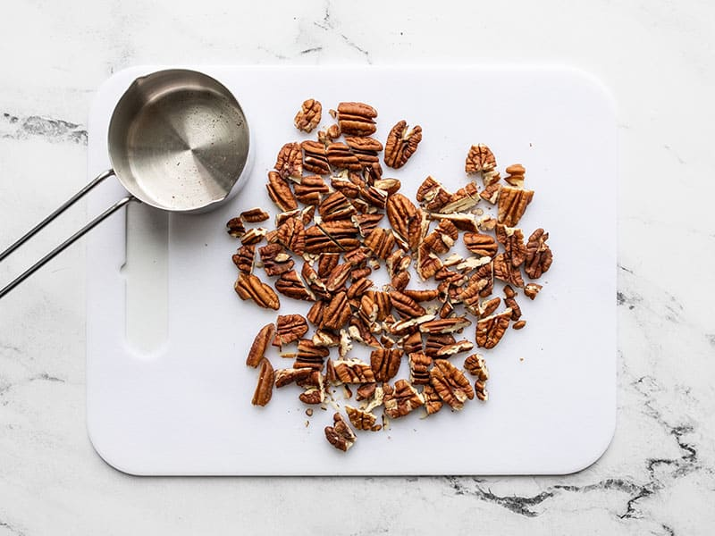 Chopped pecans on a cutting board with measuring cup