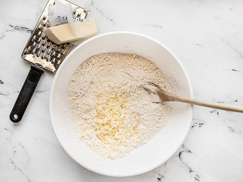 Grated frozen butter added to bowl of dry ingredients, cheese grater on the side