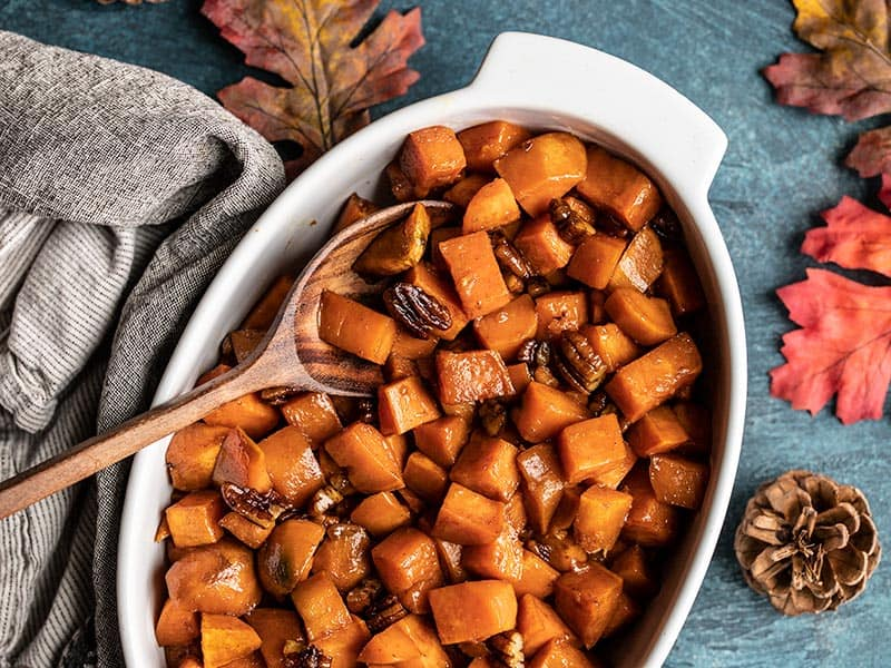 Maple Roasted Sweet Potatoes in a casserole dish with a wooden spoon on a blue background with leaves and pine cones on the side.