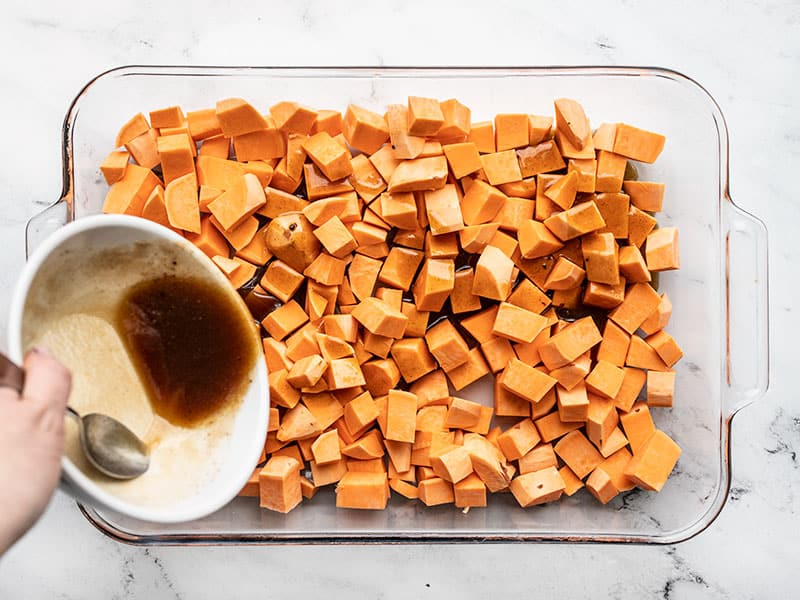 Butter mixture being poured over cubed sweet potatoes