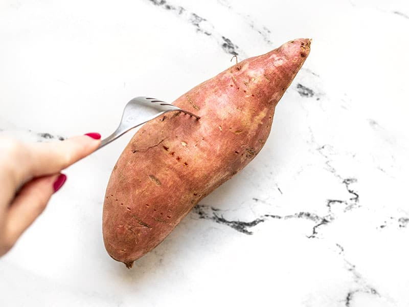 A fork pricking a raw sweet potato