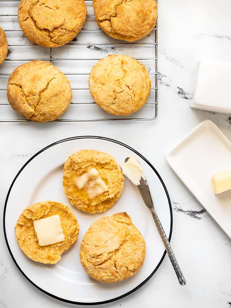 Sweet Potato Biscuits on a wire cooling rack and a couple biscuits on a plate, one open and smeared with butter