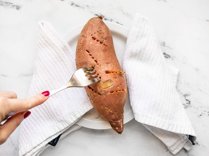 Fork poking a cooked sweet potato on a plate