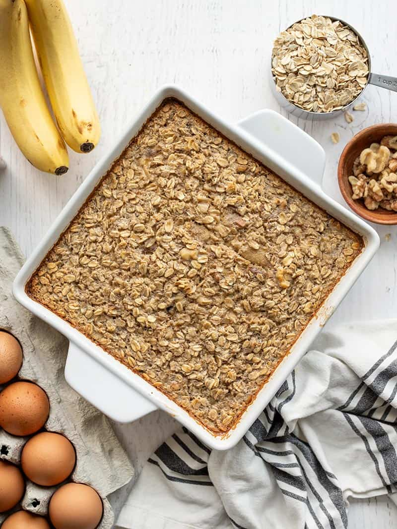 Overhead view of a casserole dish of banana bread baked oatmeal, surrounded by ingredients