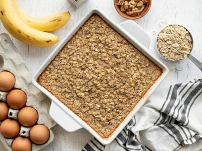 Overhead view of a casserole dish full of banana bread baked oatmeal, surrounded by ingredients
