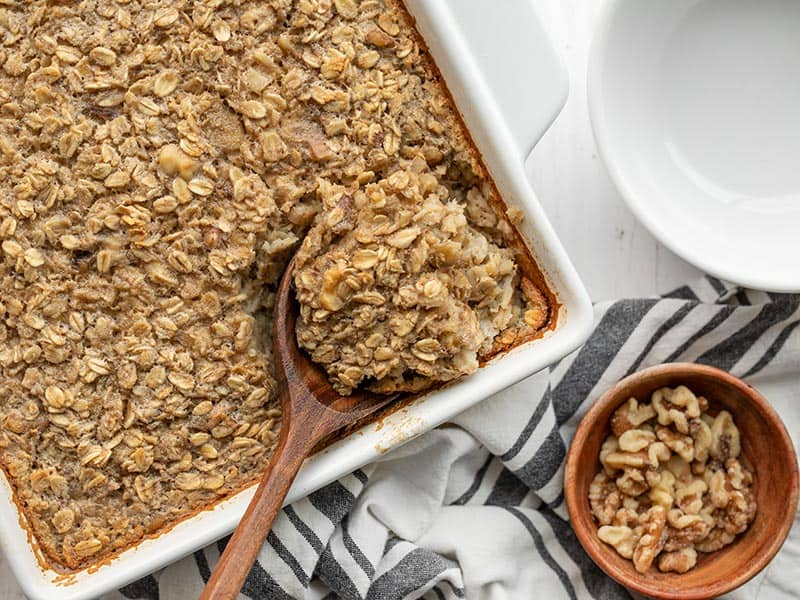 A wooden spoon scooping baked oatmeal out of the side of the casserole dish