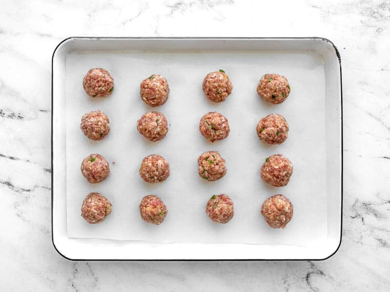 Shaped pork meatballs on a baking sheet lined with parchment paper