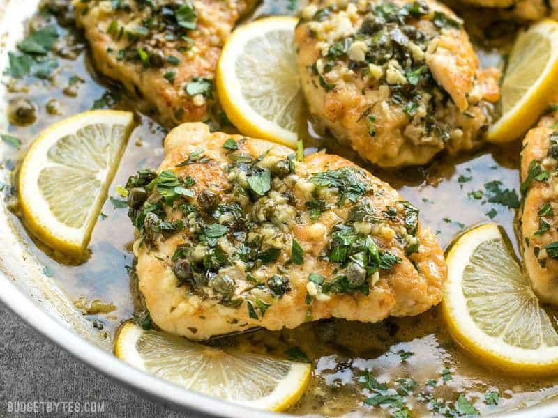 Close up of capers and parsley on top of a piece of Chicken Piccata with lemon garlic sauce.