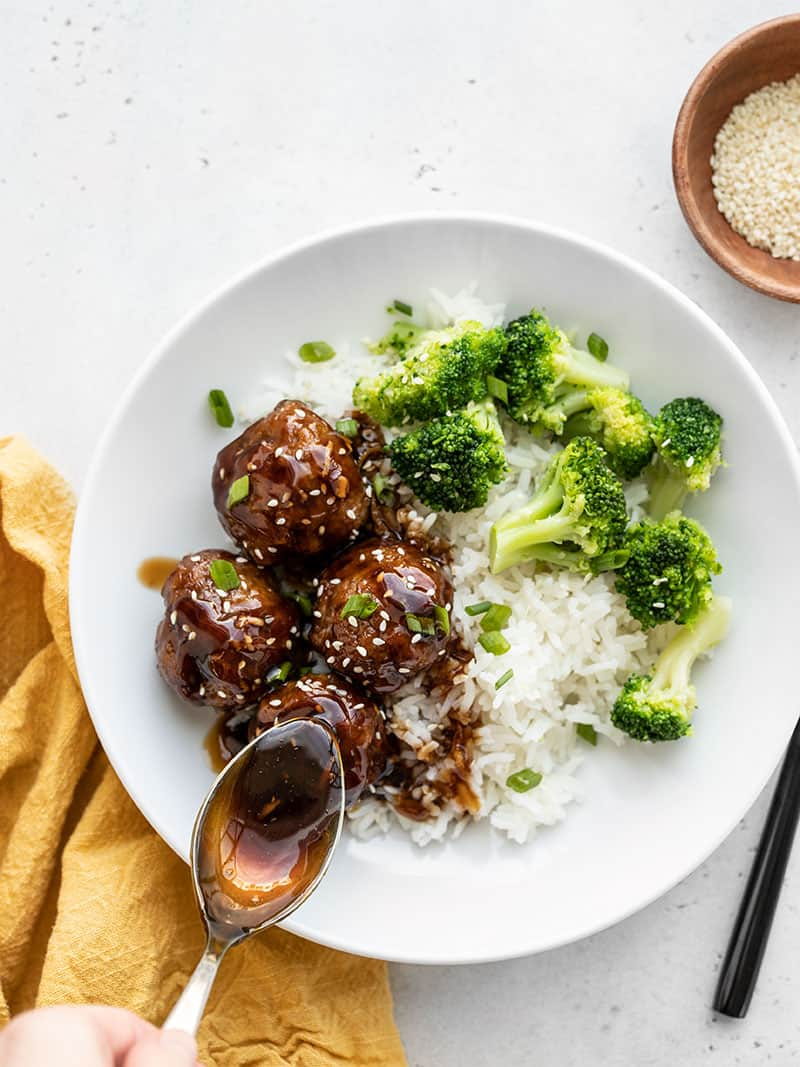 Teriyaki meatball bowls with teriyaki sauce being drizzled on top with a spoon, a bowl of sesame seeds on the side.