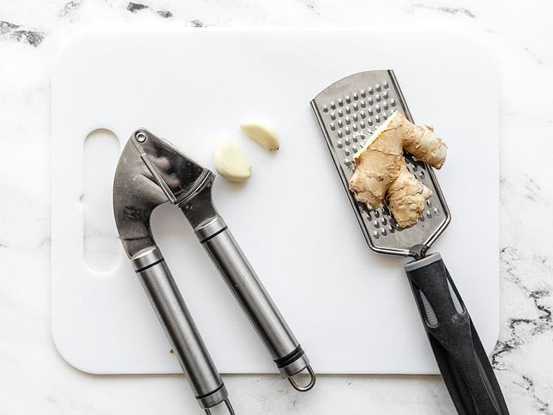 garlic press with two cloves of garlic, and fresh ginger with a microplane