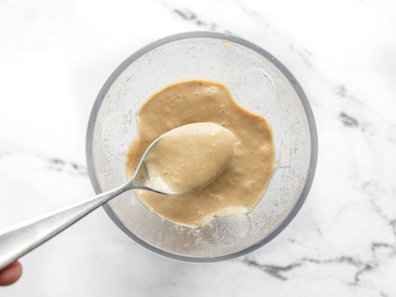 Blended dressing on a spoon in the blender