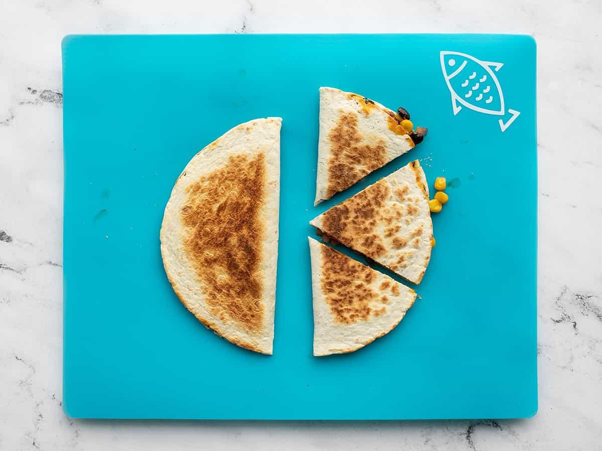 cut quesadillas on a cutting board
