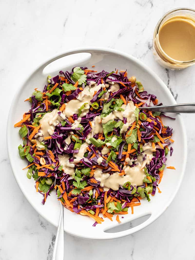 Crunchy Cabbage Salad in a white serving dish with two forks, drizzled with sesame ginger dressing