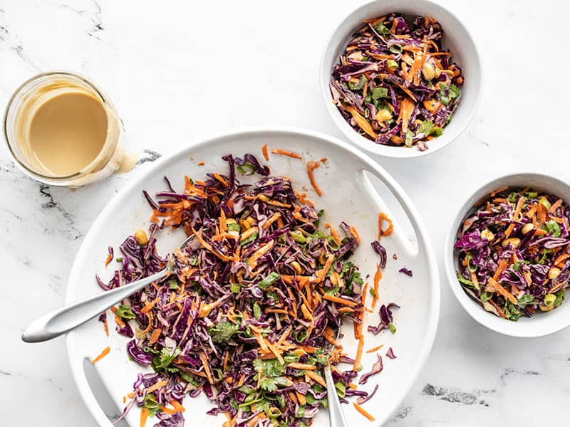 Crunchy cabbage salad coated in dressing, dished out to two bowls.