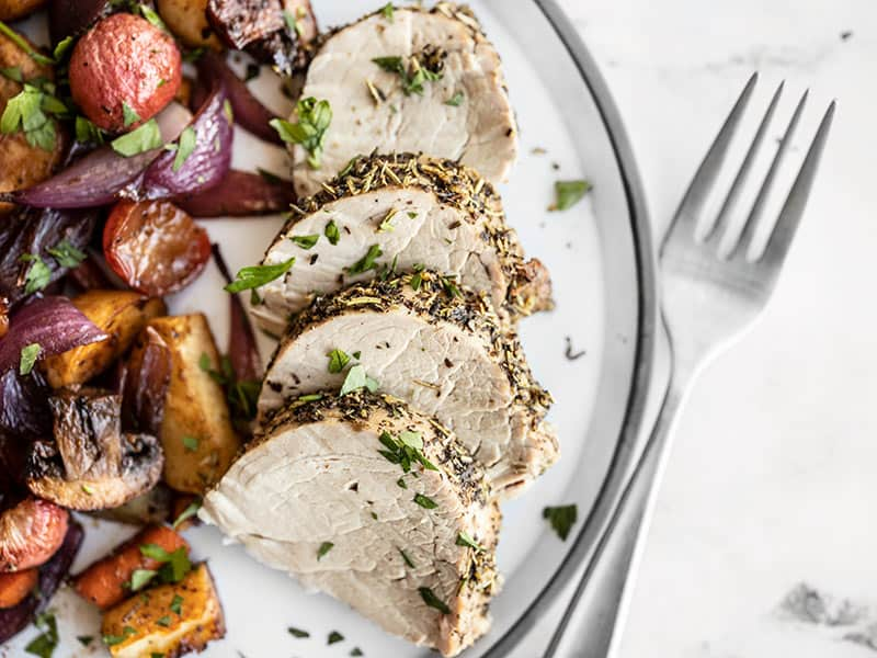Herb Roasted Pork Tenderloin Slices on a plate with balsamic roasted vegetables