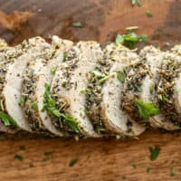 Slices of Herb Roasted Pork Tenderloin on a wooden cutting board.
