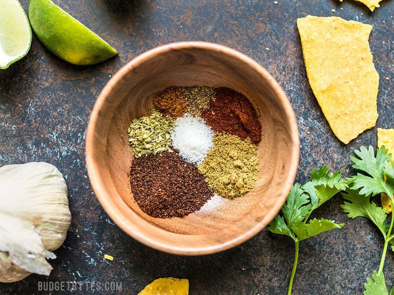 Individual spices used for homemade taco seasoning in a small wooden bowl.