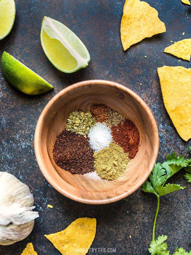 Individual ingredients for homemade taco seasoning in a small wooden bowl, surrounded by chips, limes, cilantro, and garlic.