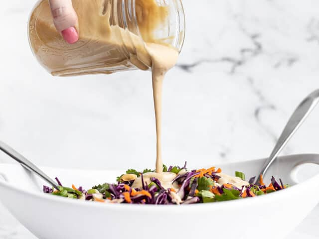 Sesame ginger dressing being poured over crunchy cabbage salad from a mason jar