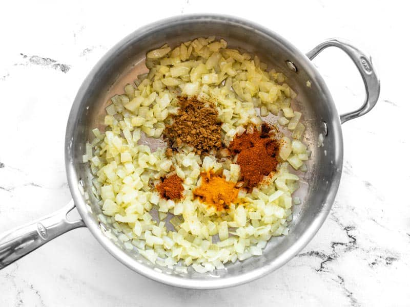 Spices added to skillet with onion garlic and ginger